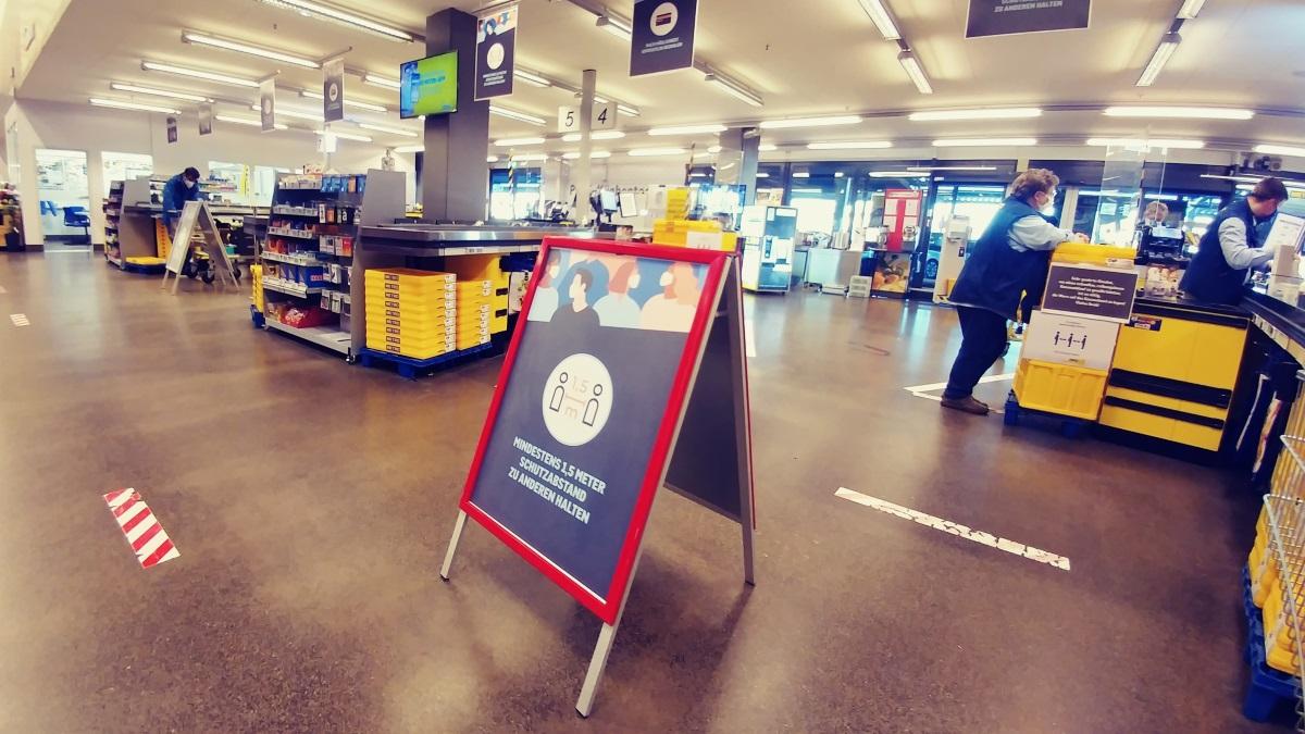 Ein Schild weist in einem Einkaufsmarkt auf die Abstandsregeln im Rahmen der Coronamaßnahmen hin.