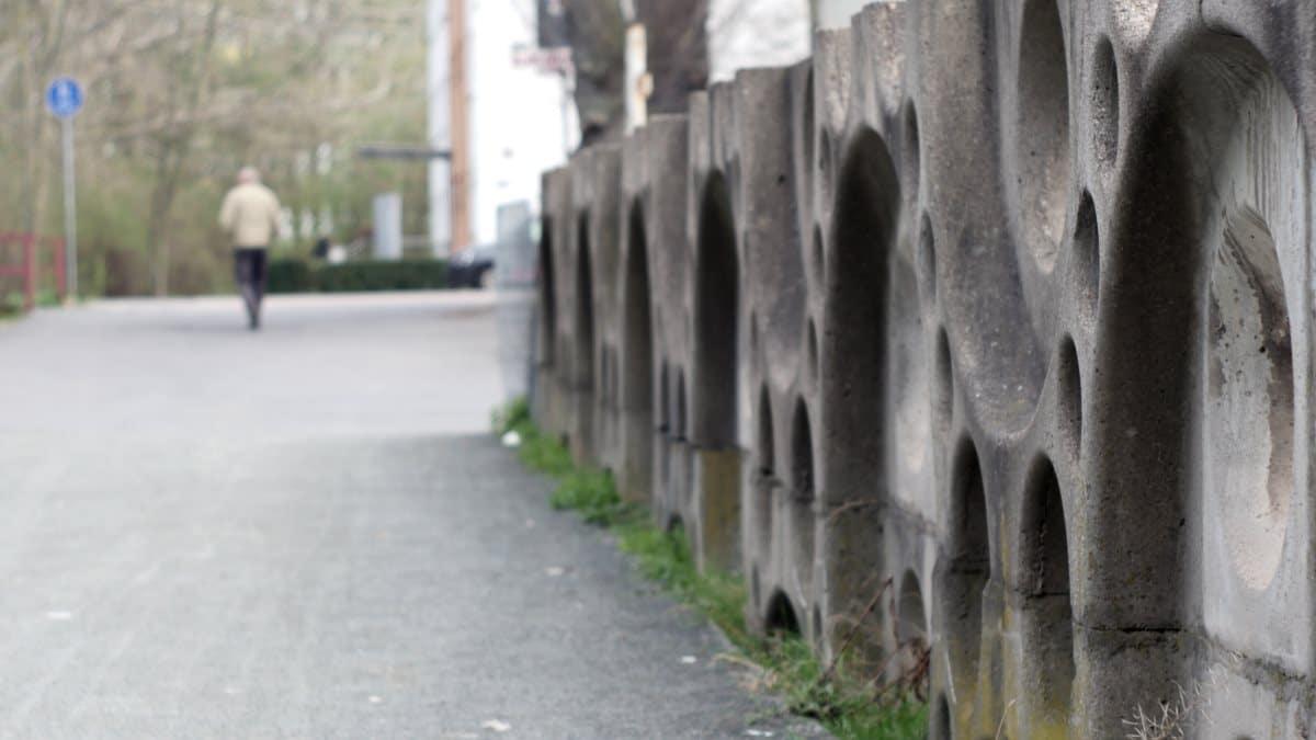 Betonzaun aus DDR Zeiten mit Fußgänger im Hintergrund